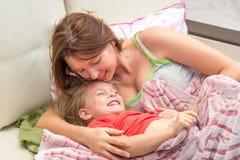 Una mujer abraza a la pequeña hija en la cama que despierta Foto de archivo libre de regalías