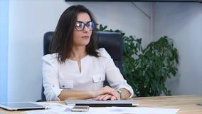 Una mujer acertada hermosa que habla en el teléfono en la oficina moderna metrajes