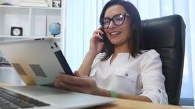 Una mujer acertada hermosa que habla en el teléfono en la oficina moderna almacen de metraje de vídeo