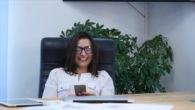 Una mujer acertada hermosa que usa el teléfono en la oficina moderna metrajes