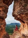 Una mujer admira el paisaje del bosque que se sienta en un agujero en una roca en los Mesas de Chapada das, el Brasil Imágenes de archivo libres de regalías