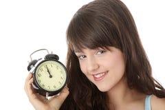 Una mujer adolescente con el reloj de alarma Imagen de archivo libre de regalías