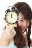 Una mujer adolescente con el reloj de alarma Imagenes de archivo