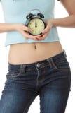 Una mujer adolescente con el reloj de alarma Imágenes de archivo libres de regalías