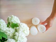 Una mujer adorna una tabla con las flores y las velas Imágenes de archivo libres de regalías