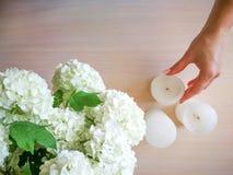 Una mujer adorna una tabla con las flores y las velas Fotos de archivo libres de regalías
