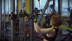 Una mujer adulta amasa su cuerpo antes de ejercitar en un simulador de los deportes almacen de video