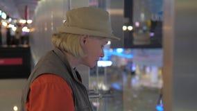 Una mujer adulta camina a la verja y mira alrededor del aeropuerto almacen de metraje de vídeo