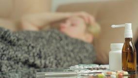 Una mujer adulta con síntomas de la enfermedad miente en el sofá bajo cubierta combinada almacen de video