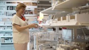 Una mujer adulta considera los artículos para la cocina, ella le gustan las mercancías almacen de metraje de vídeo