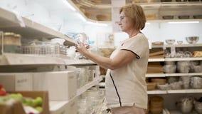 Una mujer adulta elige las placas para los postres en su cocina, en la tienda almacen de video