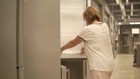 Una mujer adulta examina el refrigerador, el seigneur abre la puerta de armario almacen de video