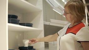 Una mujer adulta examina las tazas y las placas en la alameda, ella necesita platos almacen de video