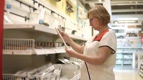 Una mujer adulta mira el precio de una cuchara de madera, que se vende en la tienda almacen de video