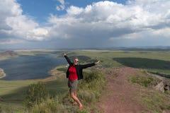 Una mujer adulta se coloca, los brazos extendidos, en una alta montaña, contra el contexto de un lago y de un cielo nublado foto de archivo