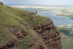 Una mujer adulta se coloca, los brazos extendidos, en un alto acantilado, contra el contexto de un lago foto de archivo libre de regalías
