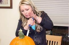 Una mujer adulta talla las calabazas de Halloween en una tabla foto de archivo libre de regalías