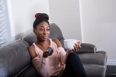 Una mujer afroamericana joven que se sienta en sofá con el telecontrol de la TV y que mira fijamente la televisión fotos de archivo libres de regalías