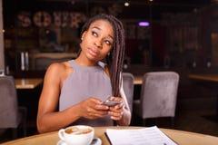 Una mujer afroamericana seria está trabajando foto de archivo