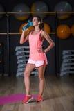 Una mujer agraciada con una botella de agua sin gas en un fondo del gimnasio Un instructor personal Forma de vida sana Fotografía de archivo