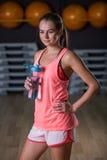 Una mujer agraciada con una botella de agua sin gas en un fondo del gimnasio Un instructor personal Forma de vida sana Fotos de archivo libres de regalías