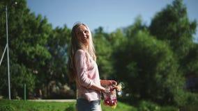 Una mujer alimenta pájaros en el parque almacen de video