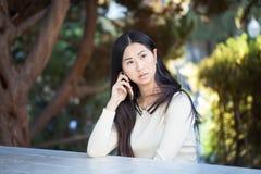 Una mujer asiática bastante seria que habla en el teléfono Imagen de archivo libre de regalías