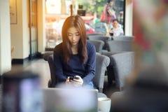 Una mujer asiática con el teléfono elegante Foto de archivo