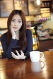Una mujer asiática con el teléfono elegante Imagen de archivo libre de regalías