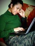 Una mujer asiática con su computadora portátil Foto de archivo