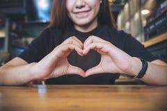 Una mujer asiática de la cara sonriente que hace la muestra de la mano del corazón Fotos de archivo libres de regalías