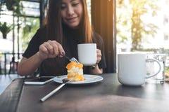 Una mujer asiática hermosa que come una torta anaranjada mientras que bebe el café en café moderno Fotos de archivo libres de regalías