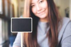 Una mujer asiática hermosa que lleva a cabo una muestra cuadrada en blanco de la pizarra Fotografía de archivo libre de regalías