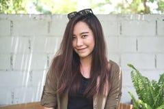 Una mujer asiática hermosa que sonríe y que se sienta en parque al aire libre con el fondo blanco de pared de ladrillos Foto de archivo