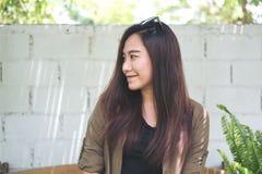 Una mujer asiática hermosa que sonríe y que se sienta en parque al aire libre con el fondo blanco de pared de ladrillos Fotografía de archivo libre de regalías