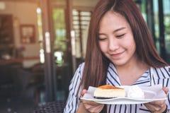 Una mujer asiática hermosa que sostiene un pedazo de pastel de queso y de crema azotada en una placa blanca con la sensación feli Fotografía de archivo libre de regalías