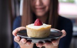 Una mujer asiática hermosa que sostiene y que muestra la tarta del queso de la fresa con la sensación feliz en el café moderno Fotografía de archivo