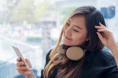 Una mujer asiática hermosa que usa el auricular y sosteniendo el teléfono elegante con la sensación feliz y se relaja en café mod Imagen de archivo libre de regalías