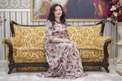 Una mujer asiática llena que se sienta en el sofá en la sala de estar Imagen de archivo