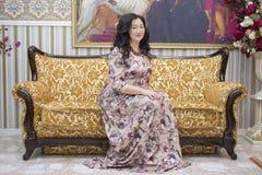 Una mujer asiática llena que se sienta en el sofá en la sala de estar Fotos de archivo