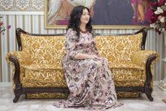 Una mujer asiática llena que se sienta en el sofá en la sala de estar Foto de archivo libre de regalías