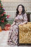 Una mujer asiática llena que se sienta en una silla en la sala de estar Foto de archivo