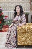 Una mujer asiática llena que se sienta en una silla en la sala de estar Fotos de archivo