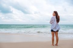 Una mujer asiática que coloca y que mira la opinión sobre la playa con el mar y el cielo azul foto de archivo libre de regalías