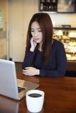 Una mujer asiática que piensa con el teléfono elegante Fotografía de archivo libre de regalías