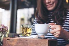 Una mujer asiática que sienta y que sostiene una taza de café caliente y de un vidrio de té en la tabla de madera del vintage Imagen de archivo