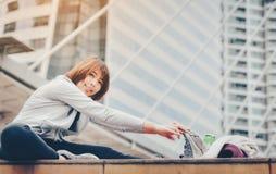 Una mujer asiática se está calentando para ejercitar en una ciudad grande cure foto de archivo