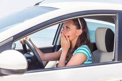 Una mujer asustada está en el coche Fotos de archivo