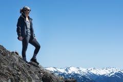 Una mujer atlética activa se coloca en el top de una montaña imagenes de archivo