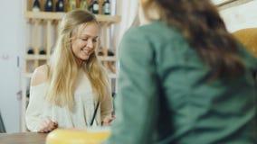 Una mujer atractiva compra comida en una pequeña tienda, la visión desde el lado del contador almacen de video